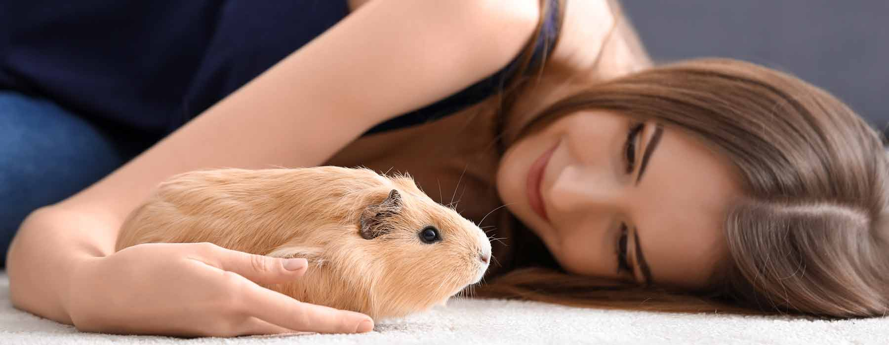 girls lying down with cute beige guinea pig